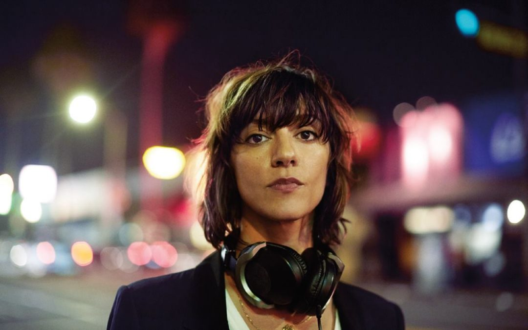 An image of director Ana Lily Amirpour. Amirpour is an Iranian-American woman in her 30s, with short brown hair and a fringe that is messy in a cool way. She wears a black suit jacket over a white top, and a pair of headphones slung around her neck. She is looking directly into the camera, poised, and the background is a blurry nighttime street with bright lights.